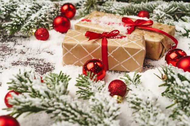 雪で粉にされた木製のテーブルの上のクリスマスプレゼント