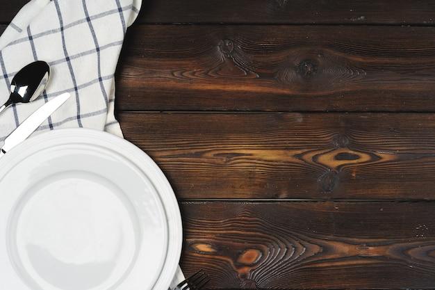 Сервировка стола с тарелками на темной деревянной стене