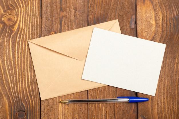 白紙の紙と木製のテーブルの上にペン