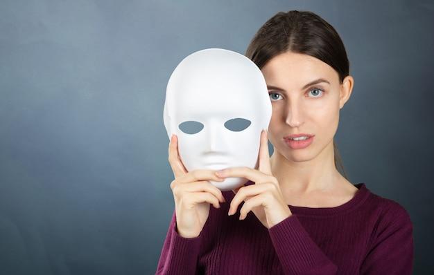マスクを持つ素敵な女性の肖像画。女性の感情と気分の概念