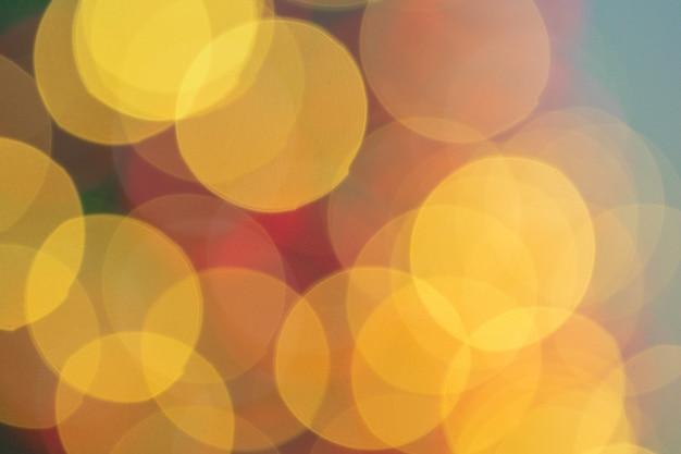 黄金色の輝きの背景を持つクリスマスライトボケ