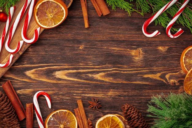 装飾が施された木製の机の上のキャンディー杖とクリスマスの背景