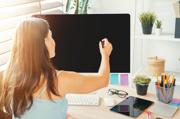 彼女のオフィスでの仕事で若い女性のグラフィックデザイナー
