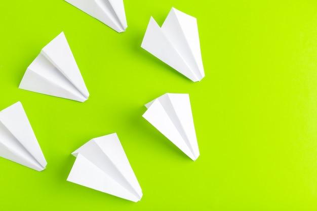 グリーンパステルカラーの背景に紙飛行機のフラットレイアウト