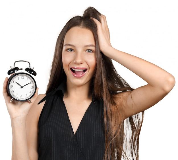 時計を保持している若い女性。時間管理の概念