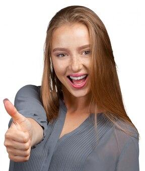 Счастливая молодая женщина с большими пальцами руки вверх