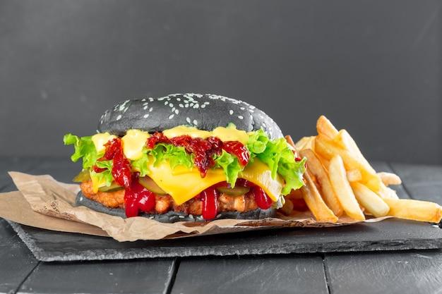 Гамбургер с картофелем фри на грифельной тарелке