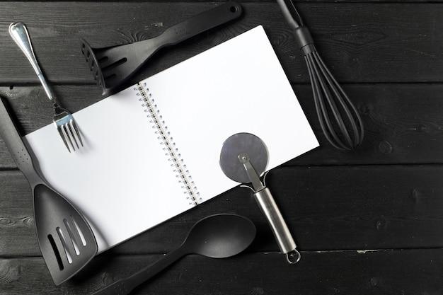 テーブルクロス、コピースペースを持つテーブルに開いたメモ帳と台所用品の空白のシート
