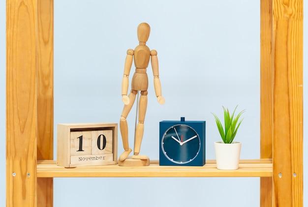 Деревянная полка с будильником и предметы на синем фоне