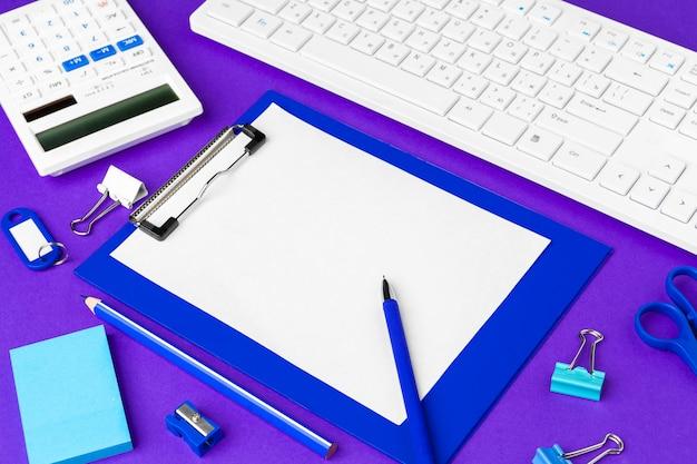 紫色の背景にオフィスライフスタイルアイテムの組成、オフィスの机の上のコンピューターキーボードオフィス用品