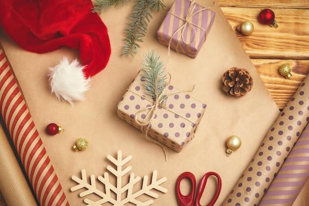 クリスマスのお祭り気分。装飾、リボン、ギフト用紙、木製の背景に包まれたギフトのフラットレイアウト