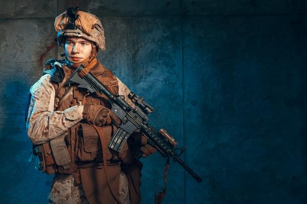Спецназ солдат или частный военный подрядчик держит винтовку. изображение на темном фоне