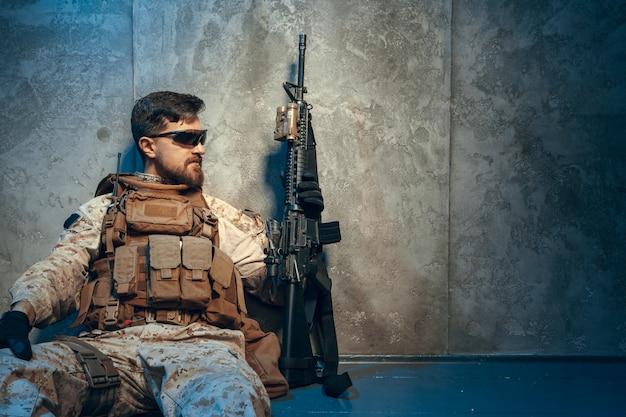 アメリカの民間軍事請負業者がライフルを保持しています。暗い背景上の画像
