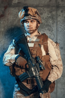 Полностью экипированный солдат в камуфляжной форме и шлеме, вооруженный пистолетом и штурмовой винтовкой