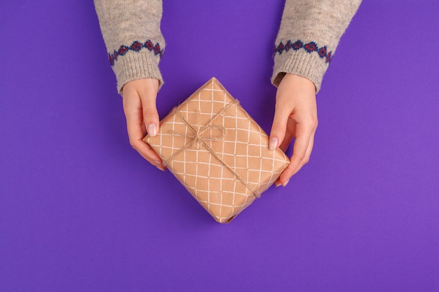 紫色の背景に包まれたギフトを保持している女性の手