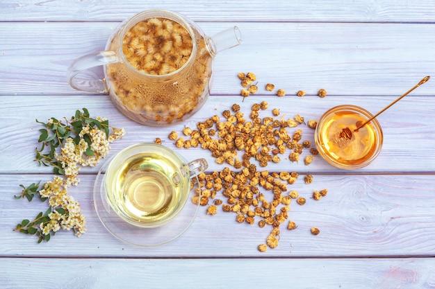 ガラスカップで健康的なカモミールティー。ティーポット、小さな蜂蜜の瓶