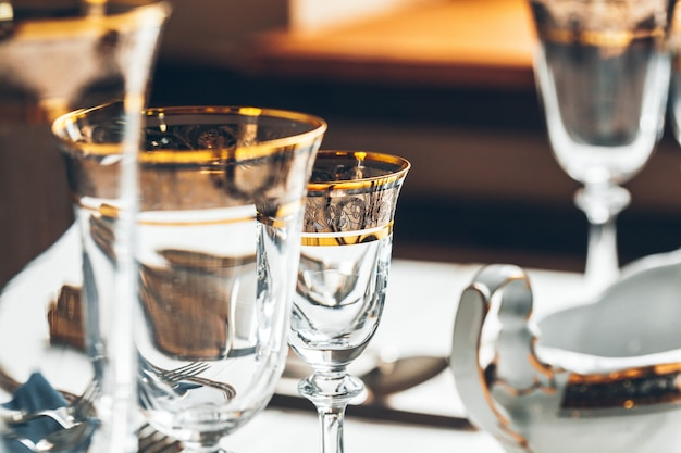 カトラリーやガラス製品を使った高級ダイニングのテーブルセッティングのショットを閉じる