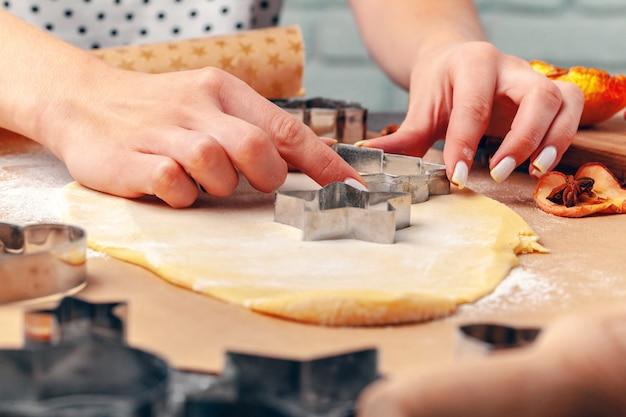 自宅で新鮮な生地からクッキーを作る女性の手