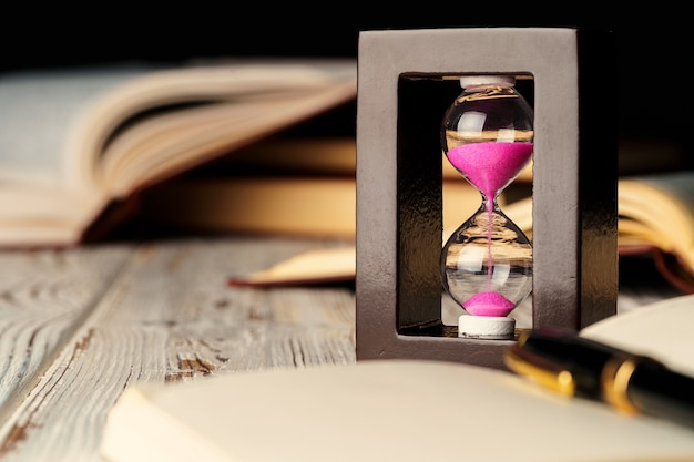 Песочные часы на деревянный стол с открытой книгой крупным планом