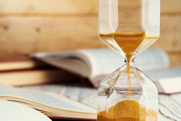 Песочные часы с песком крупным планом на деревянном фоне