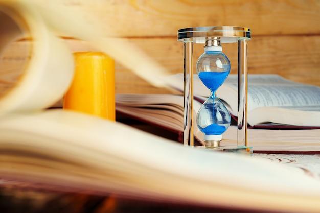Часы с песочными часами крупным планом на столе