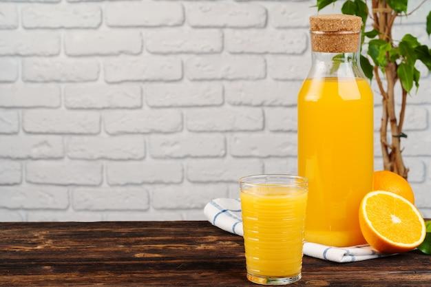 白いレンガ壁の背景に木製のテーブルに新鮮なオレンジジュースのボトル
