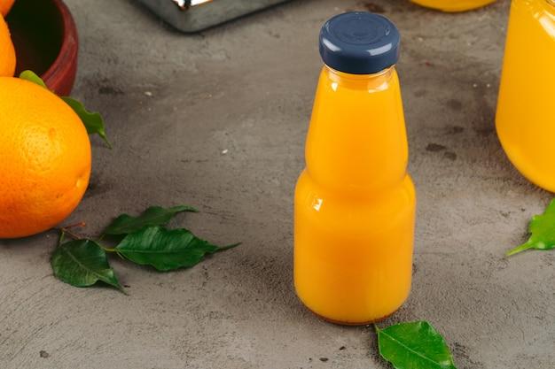 木製のテーブルにオレンジとオレンジジュースのボトル