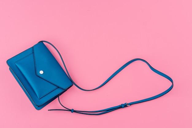 明るいピンクの背景に女性の小さなハンドバッグクラッチ