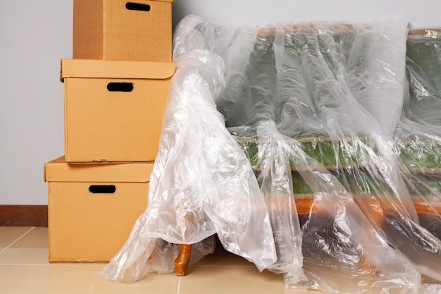 箱に詰めた家庭用品と移動用の梱包済みソファ