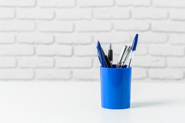 Ручки или письменные принадлежности на белом столе