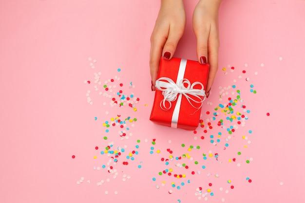 Женщина держит подарочную коробку на цветном фоне