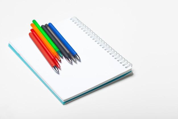 白い背景で隔離のメモ帳ノートとボールポンペン