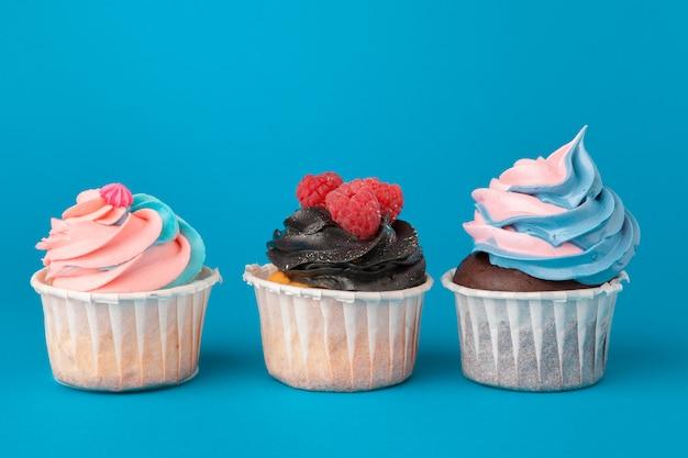 青色の背景に誕生日カップケーキをクローズアップ