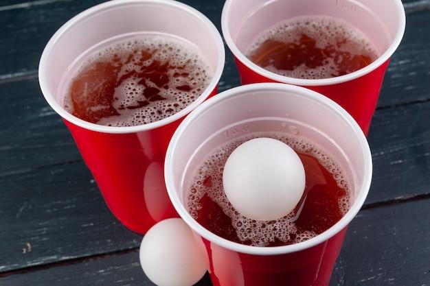 赤いカップとビールピンポンのボールと木製のテーブル
