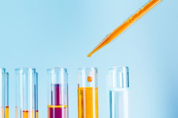 Лабораторные пробирки с красными и желтыми жидкостями на голубом фоне