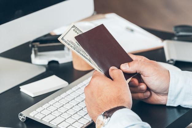 オフィスで彼の手でドル紙幣とパスポートを保持している実業家のクローズアップ