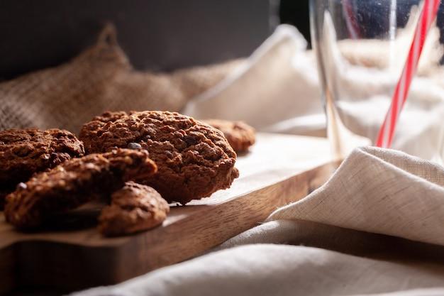 ミルクのガラスとチョコレートのシャキッとしたクッキーをクローズアップ