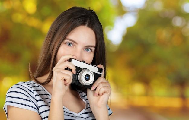 Портрет молодой улыбающейся женщины снимающей с ретро камерой