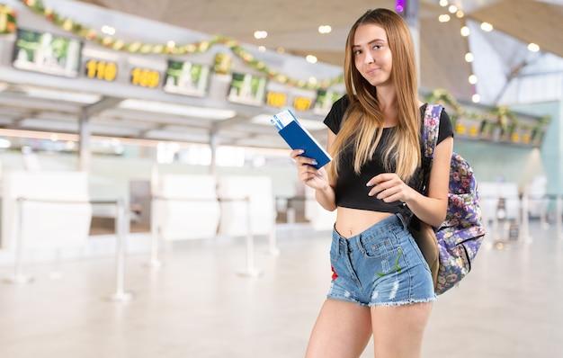 Молодая женщина, держащая посадочный талон в аэропорту