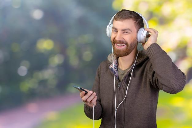 ヘッドフォンで音楽を聞いて幸せな若い男