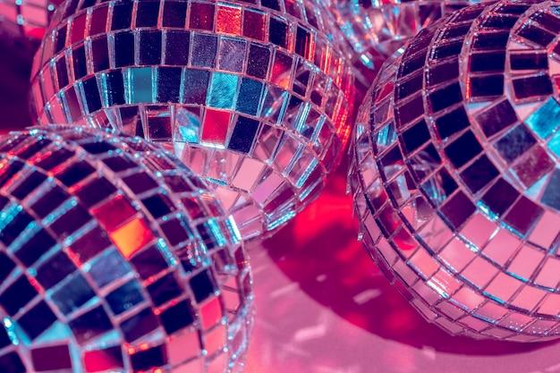 ピンクの背景の上のディスコボールをミラーします。パーティー、ナイトライフのコンセプト