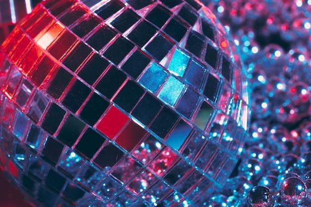 光を反射するミラーボールと光沢のあるディスコパーティーの背景