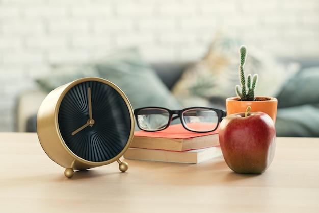 学校の時間です。ビンテージの目覚まし時計と木製の机の上のリンゴ