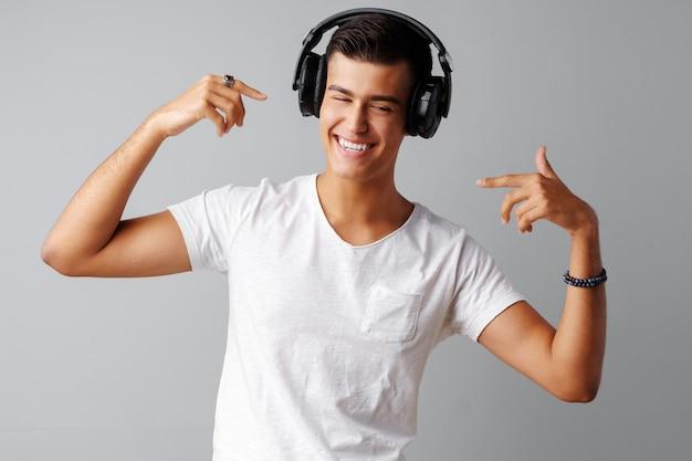 Подросток молодого человека слушая к музыке с его наушниками