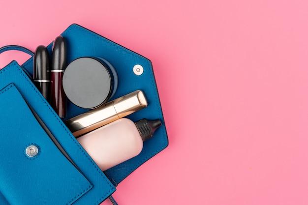 化粧品でいっぱいの女性の小さなハンドバッグ