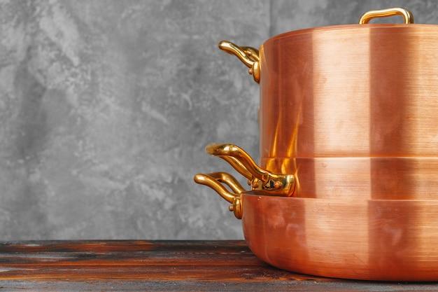 木製テーブルの上の銅鍋のスタックをクローズアップ