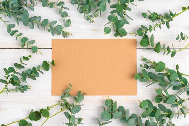 木製の素朴な背景に花の枝に囲まれたコピースペースを持つ空の手紙