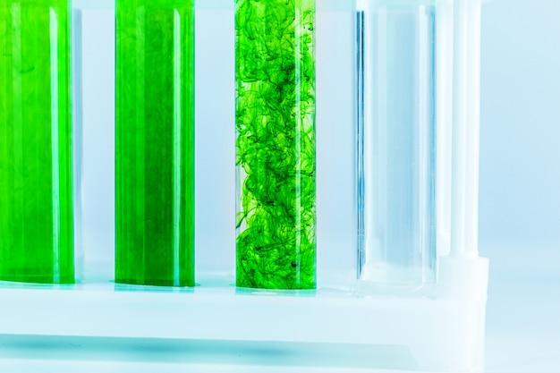 Зеленые жидкости в пробирках в химической лаборатории крупным планом