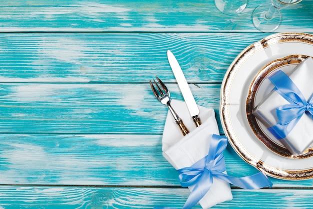 青い木製の背景に美しいテーブルセッティング