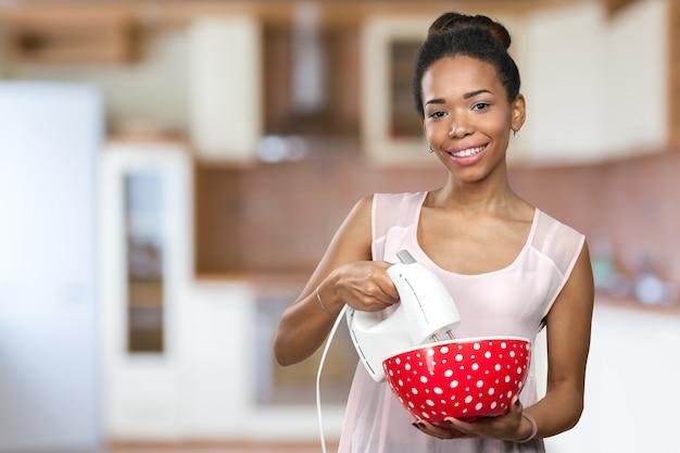 台所用品を保持しているアフリカ系アメリカ人の女性